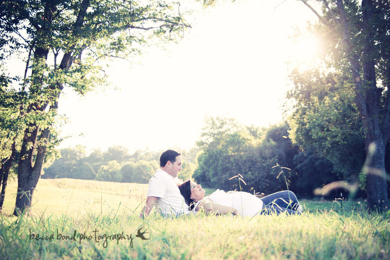 pregnant couple laying in the grass by becca bond photographer
