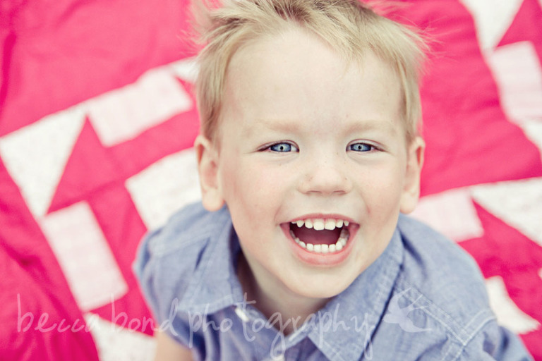 child's photography portrait of a little boy laughing on a blank
