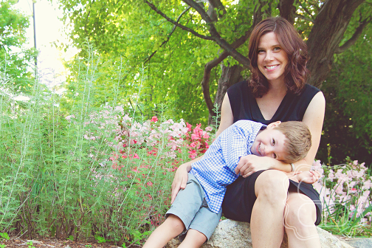 Mother and child snuggle among flowers at a park