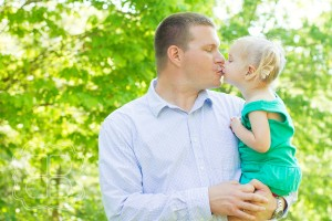 Child and daughter kiss in this family picture