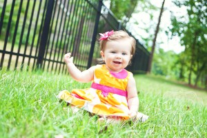 Baby girl in colorful dress smiles big for photographer