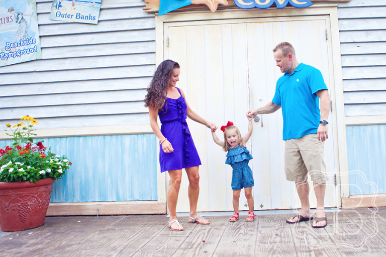 Family poses with their child in Charlotte NC's Carowinds for picture