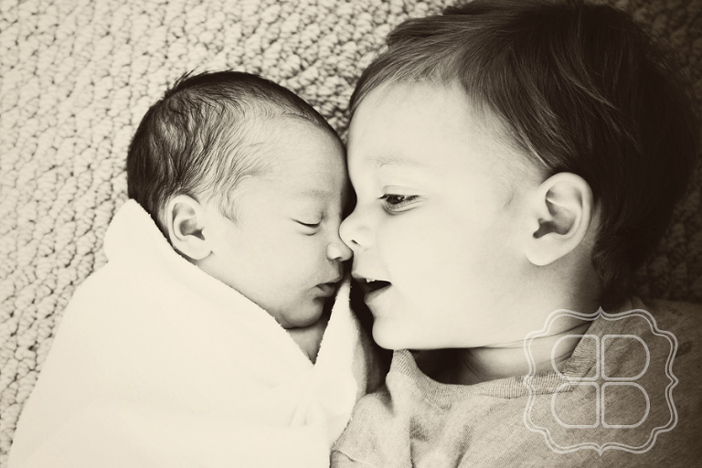 Child snuggles his sleeping baby sister