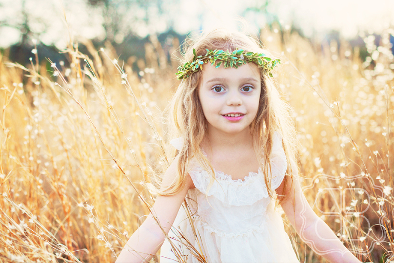 pretty little girl in a field with wreath on her head