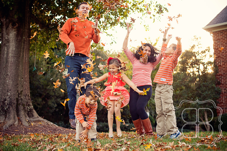 family playfully tosses autumn leaves