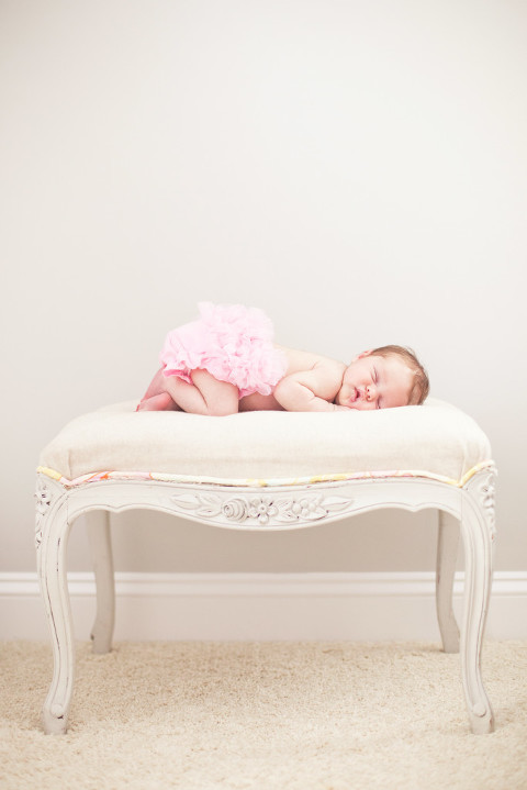 Charlotte Baby Photographer arranges beautiful newborn on a vintage stool in a pink ruffled tutu.