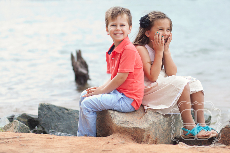 brother and sister laugh with photographer