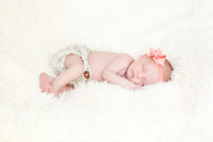 Sleepy Newborn baby with bow