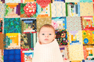 Modern portrait of a baby on vintage quilt