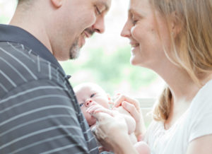 Parents love as they hold their adopted newborn.
