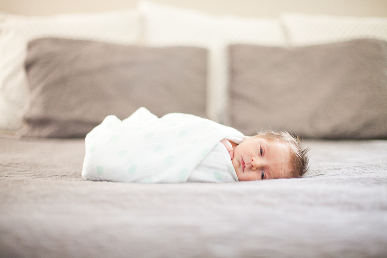 Lifestyle photo of a newborn baby on parents bed