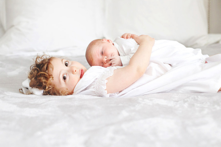 Curly hair child with baby brother
