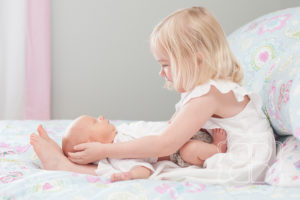 Big sister holds baby brother